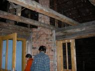 No ceiling, floor, or windows; bare log walls and a lot of cobwebs