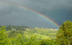 Rainbow lights up the village, but the storm has hidden the Bucegi Mountains