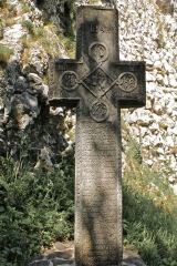 Ancient cross below Bran Castle, with power symbols and runic writing